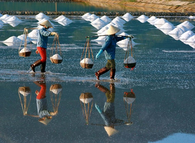 Họ gánh muối đi trên mặt ruộng sâm sấp nước mặn. Ở đồng muối Hòn Khói chủ yếu là phụ nữ làm việc gồng gánh, đàn ông thường làm các công việc khác. Trong số này có nhiều người làm thuê, gánh thuê lấy tiền công.